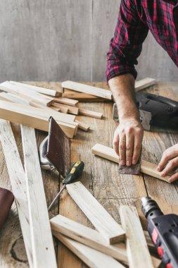 Carpenter working in carpentry workshop. Man sanding manually plank