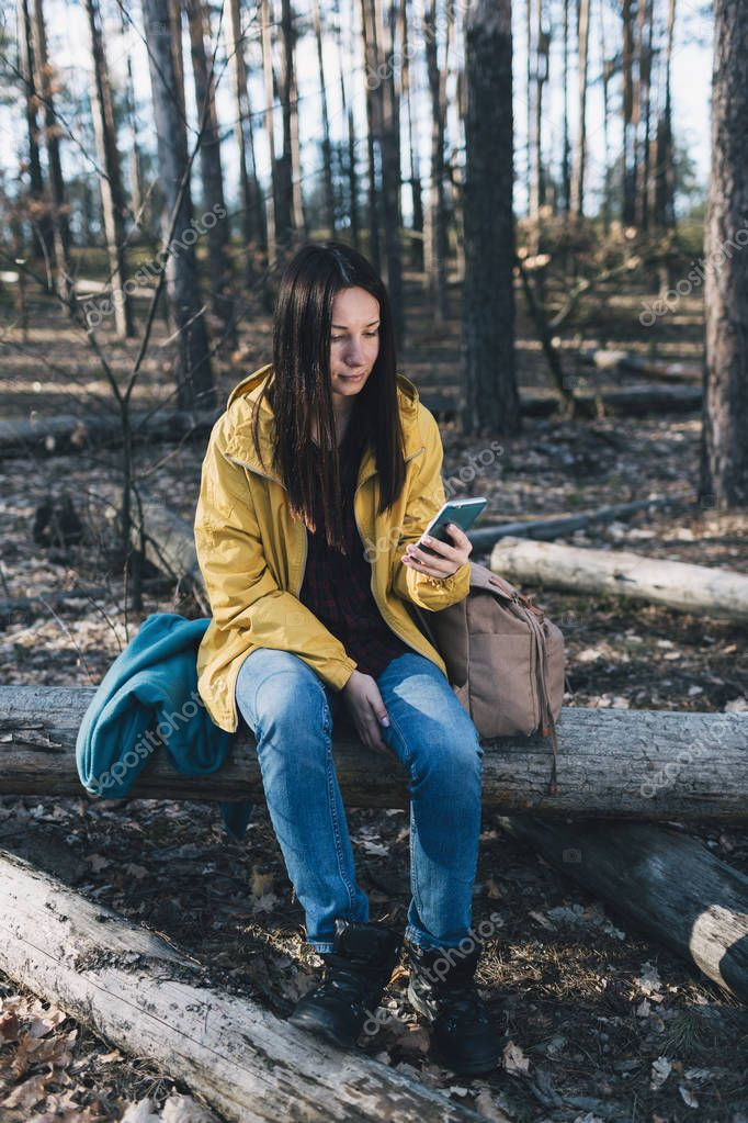 Young beautiful woman communicates internet using smartphone sitting forest