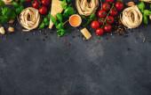 Iettuccine se složkami pro vaření italských těstovin na tmavém pozadí, horní pohled