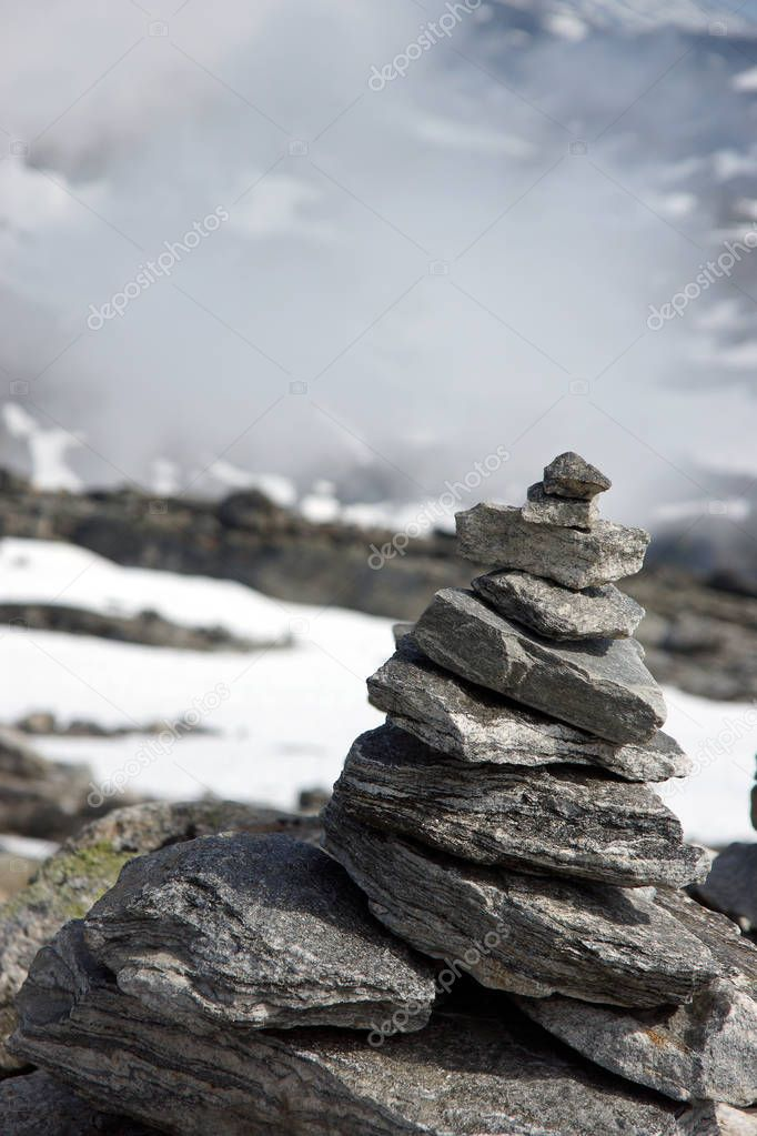 Pyramid of large stones on top of a high mountain above the clouds.