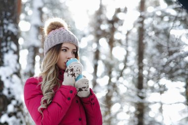 Pretty woman in burgundy coat hold blue thermo cup and drink hot coffee or tea and warm up in winter forest. Winter holiday concept - Image