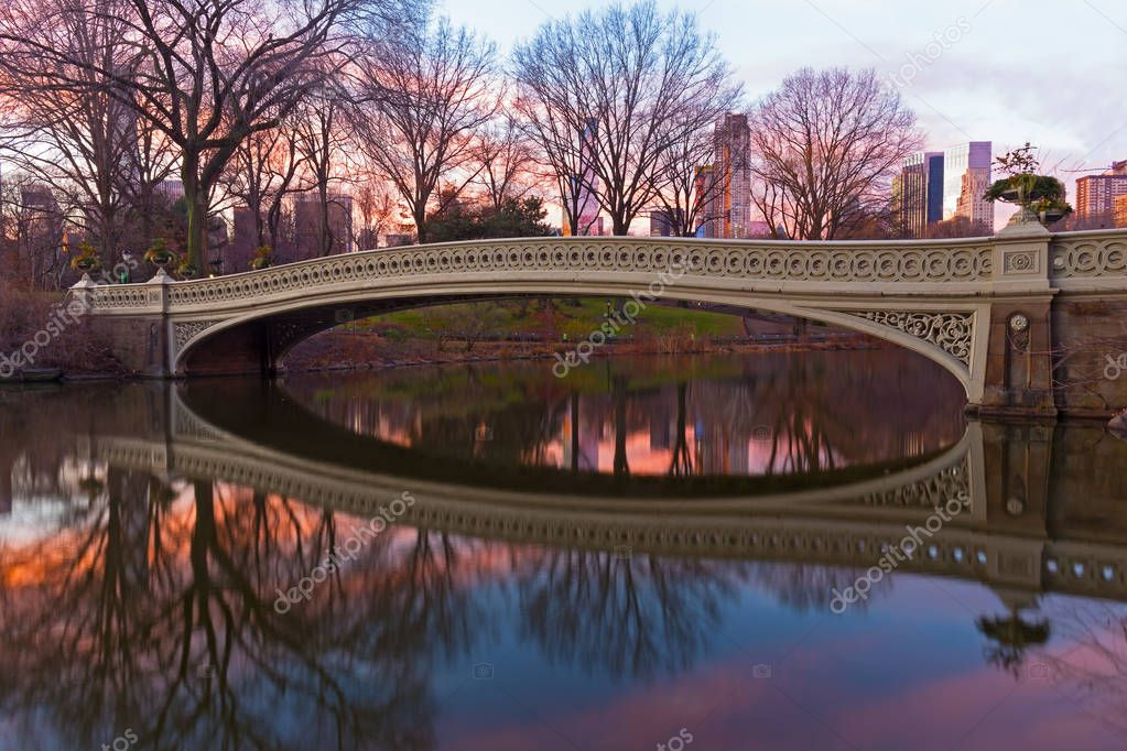 Bow Bridge at sunrise in Central Park, New York. The largest pedestrian bridge in the park decorated by planting urns looks spectacular with Manhattan buildings background.