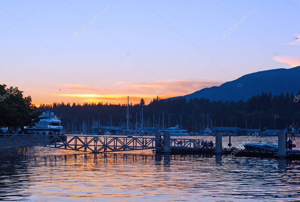 Vancouver Harbor with moored vessels at sunset, Vancouver BC, Canada. Beautiful sunset with clear skies and mountains on horizon.