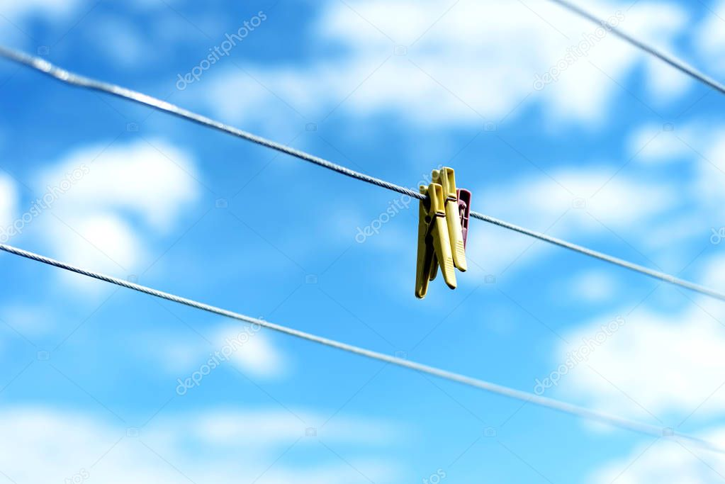 Three Plastic Clothes pegs on a Washing Line