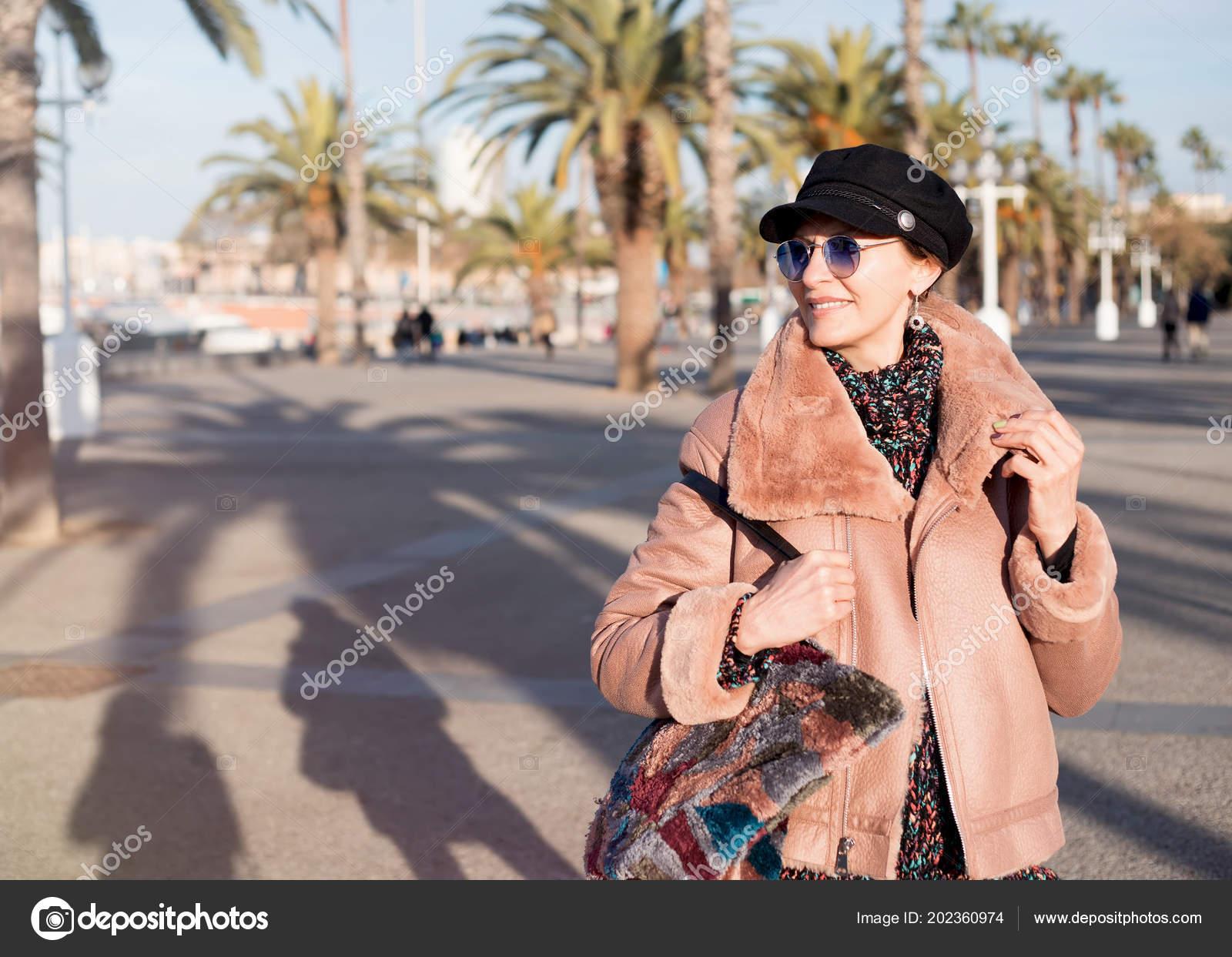 25944bbae5920 Séduisante milieu adulte femme souriante. Proche jusqu'à belle femme  élégante qui marche en manteau rose de mode, casquette rétro tenant sac,  souriant, ...