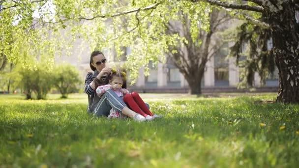 Matka s její dcerou sbírat pampelišky v parku a vazba věnec z květin