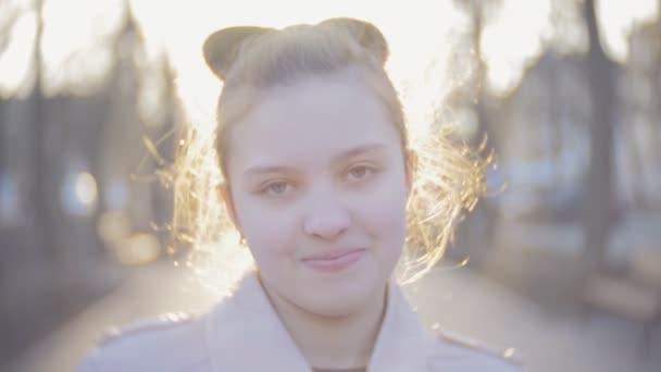 Portréja egy vonzó fiatal tini lány néz a kamerába, és mosolyog. Szoros lövés