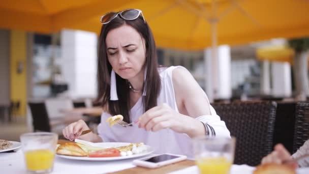 Woman having Breakfast in a street restaurant