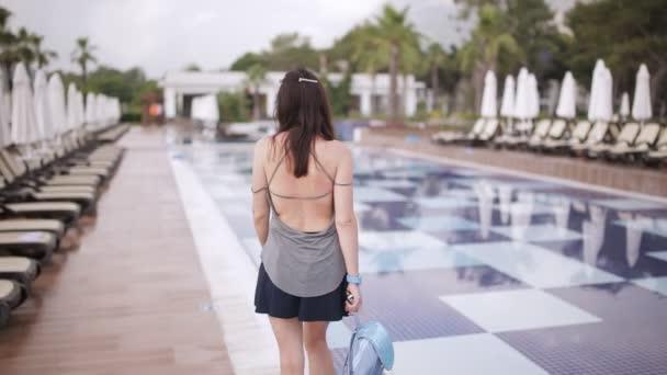 krásná dívka v šatech a s batohem, chůze v blízkosti bazénu
