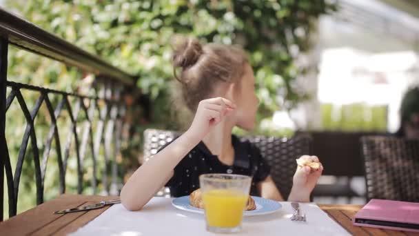 Rozkošný dívka snídáš ve venkovní kavárně. Rozkošný dívka pití čerstvé šťávy a jíst rohlík na terase