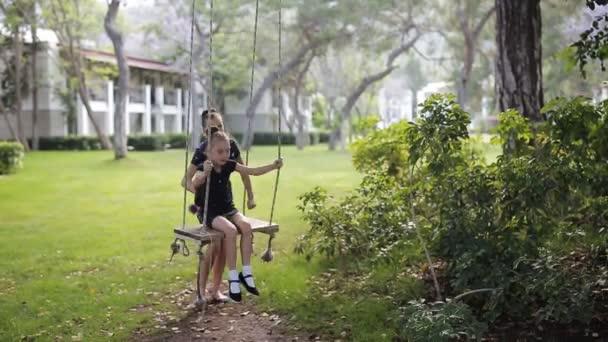 die ältere Schwester schüttelt ihre tochter auf einer schaukel unter einem baum in der sonne. Mädchen lacht, freut sich. Familienspaß im Park, im Wald, in der Natur. ein warmer Sommertag.