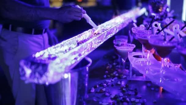 Ohnivé stopě a tabulka Ládin s koktejly na večírku. Detail ruce barmana širokou škálu koktejlů