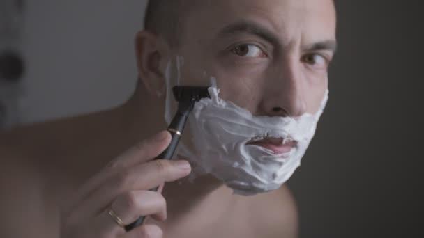 Man shaves his face. Man shaving with foam and manual razer. Close up of man shaving beard.