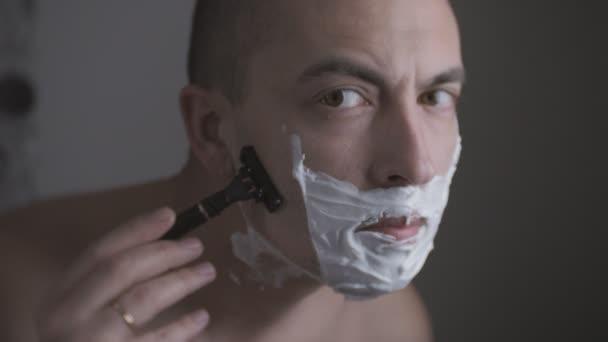 Man shaving with foam and manual razer. Close up of man shaving beard.