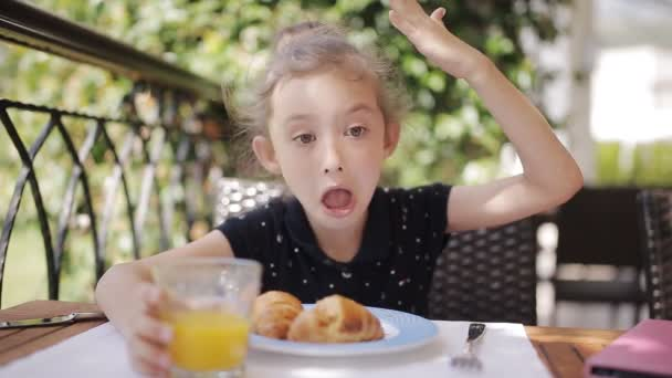 Adorable girl drinking fresh juice and eating croissant on terrace
