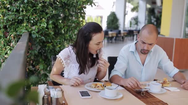 Young couple eating and talking during breakfast by table in the outdoor cafe