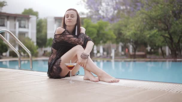 Sexy woman in swimsuit sitting thoughtfully on the edge of the pool with a Martini