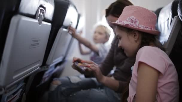 Familie fliegen in den Urlaub auf einer Ebene Zeit durchläuft Zeitschriften und smartphones