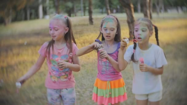 Skupina děti hrají společně vyfukuje bubliny baví v parku, zpomalené