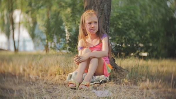 Malá holčička rozmazaně s barvami Holi pláč, sedí na stromě