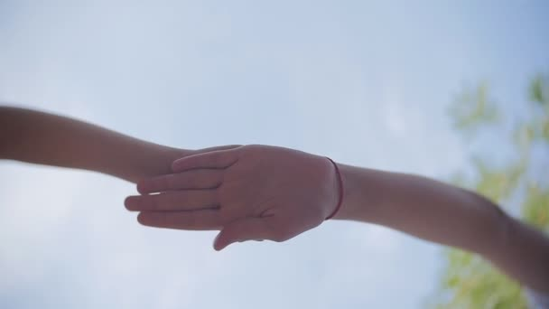 Successful team: many hands holding together on sky background in slowmotion.