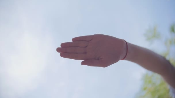 Many hands together over sky and trees in slowmotion.