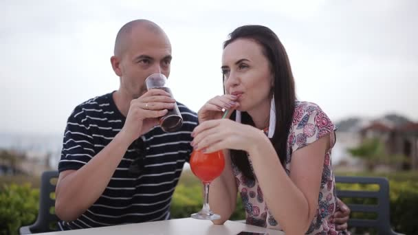 man and woman drinking cocktails in a cafe outdoors