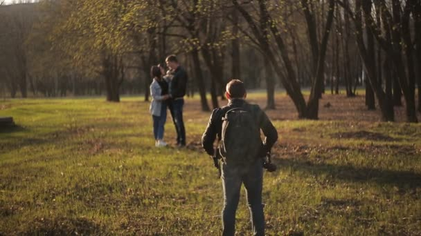 Professional photographer photographing young loving couple on nature in the Park.