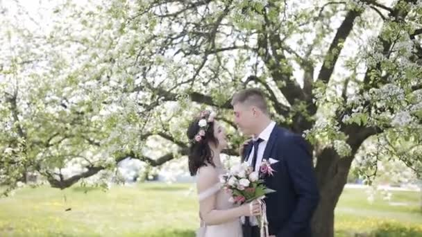 bride and groom kissing near a tree