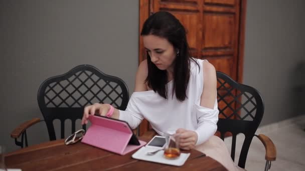 Business woman in a street cafe drinking Turkish tea and uses the smartphone