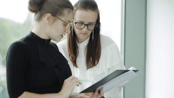 Dvě mladé krásné ženy popisují různé dokumenty v systému windows
