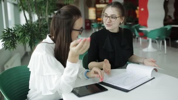 Vista dallalto su due donne graziose, giovani professionisti, Influenzatore social marketing e creatività. Incontro di lavoro in ambiente informale, discutere futuro brand strategy e la pianificazione di avvio