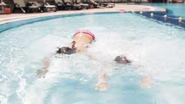 dospívající dívky plavání a potápění v bazénu a ukazují palec