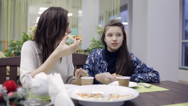 beautiful mother with her daughter eating pizza and talking cheerfully
