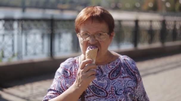 Portrét starší ženy jíst zmrzlinu v vafle kužel stojící na nábřeží