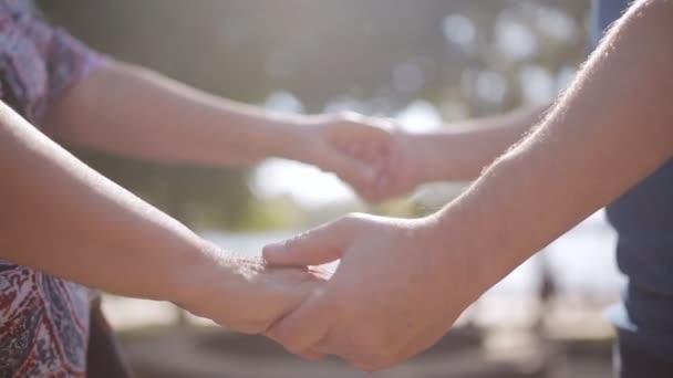 Detail z rukou staré prarodiče v sunny Park. Detail babička a děda, drželi se za ruce v parku při západu slunce