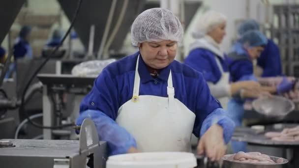 Továrna na jídlo. Pracovník vytvoří klobásy na zařízení pro výrobu automatických potravin