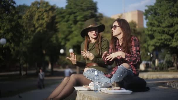Dvě dívky v láska oběd sendviče v parku a mluvit. Městská piknik v parku. Dovolená sendvič
