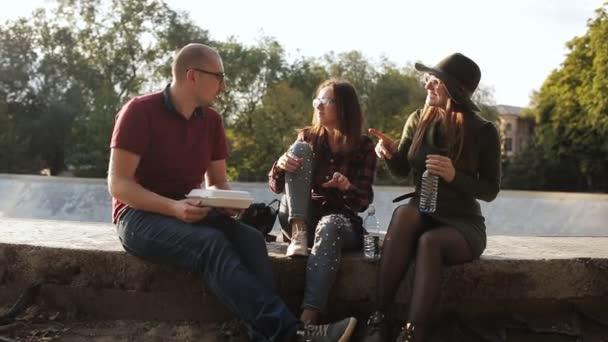 Muž a dvě dívky jsou relaxační ulice města, Bavíte se a jíst. Přátel se baví na obědě na ulici