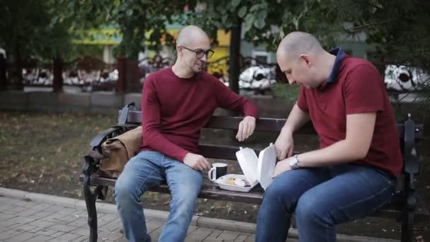 Muži na lavičce v parku jíst sendviče s hranolky, pití káva z poháry a mluví