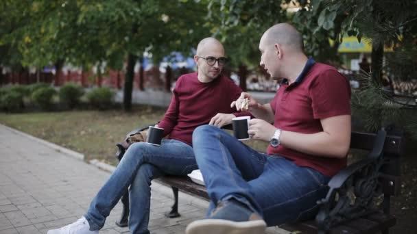 Večerní občerstvení po práci na lavičce v parku. Dva muži jsou jíst sendviče a pití káva z poháry na lavičce v parku
