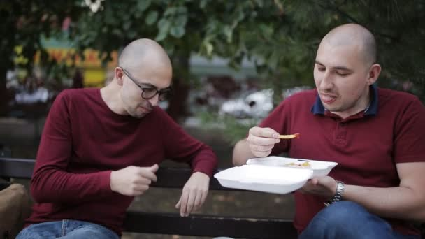 Dva muži mluví, zatímco sedí na lavičce v parku a jíst sendviče