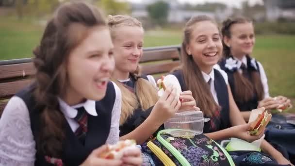 Vysokoškoláků na lavičce v parku, jíst sendviče, směje se a mluví. Šťastný, mladí přátelé, jíst oběd na lavičce v školního