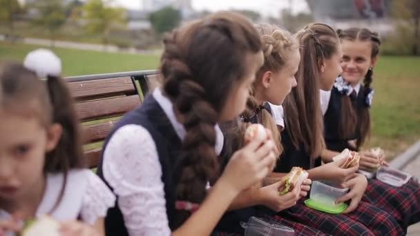 Lányok főiskolai hallgató visel az azonos iskola egységes eszik szendvicseket, és mosolyogva, miközben pihen a parkban