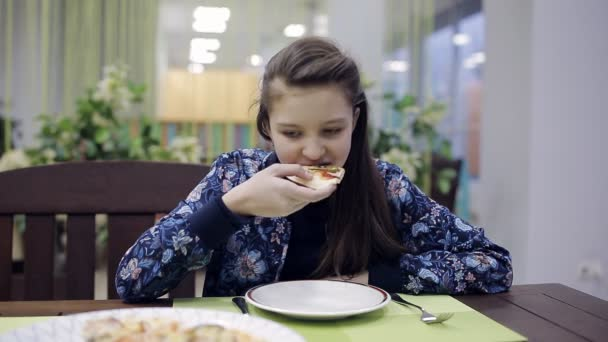 girl teenager having dinner in a pizzeria. Unhealthy food in fast food