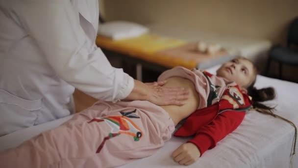 ältere Frau, der Arzt macht eine kleine Bauchmassage Mädchen in einem Massageraum im Krankenhaus