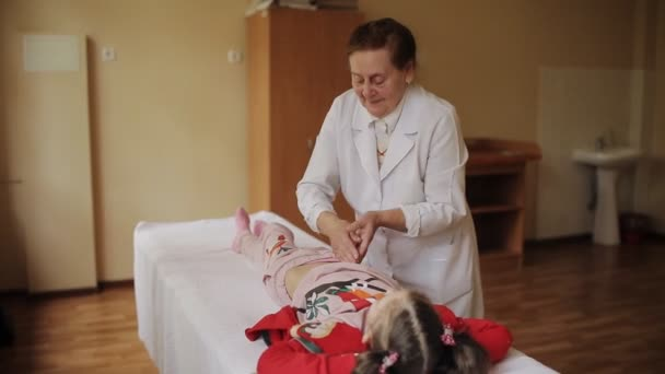 die ältere Masseurin massiert den Bauch des kleinen Mädchens im Krankenhaus.