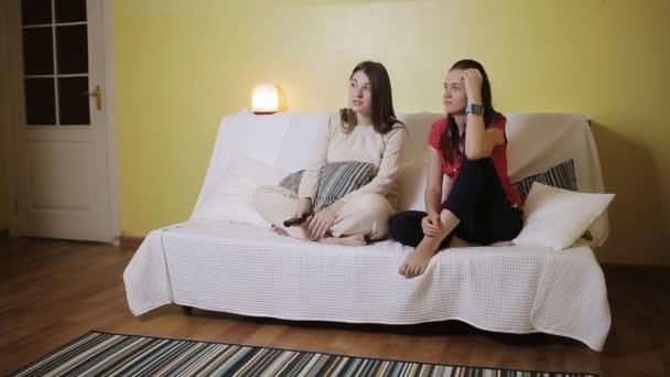 Dvě ženy přítelkyně sledování televize společně na gauči doma