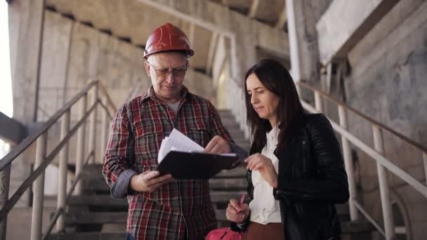 Žena inženýr a foreman v helmě porovnat prohlášení pro stavební materiály a potvrdit datum dodání objektu.