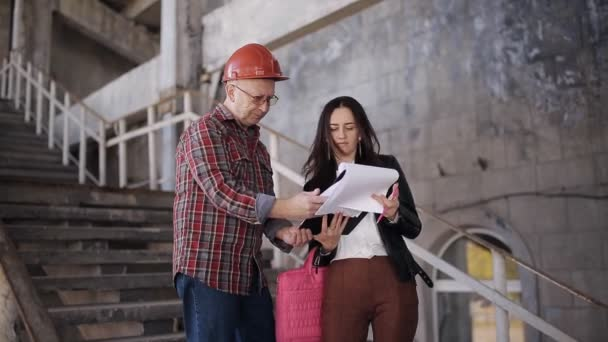 The woman engineer and the foreman in helmet compare statement acquired for construction materials and confirm the date of delivery of the object.
